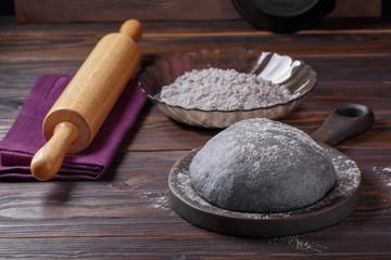 Black yeast dough on dark wooden table. Color dough for black Halloween pizza or bun.