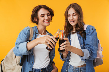 Happy women friends isolated over yellow wall background drinking soda.