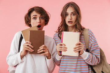 Shocked women friends isolated over pink wall background holding books.
