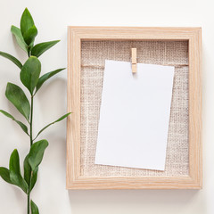 A wooden mockup frame on a white background with a sprig of green leaves on the left
