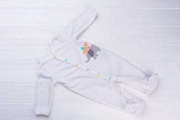 White footed baby pajama on wood.