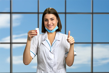 Smiling doctor with white bottle of pills. Happy cheerful female physician holding pills and showing thumb up sign on sky window background.