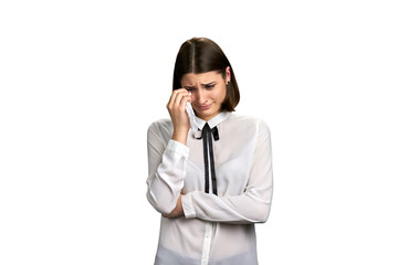 Portrait of unhappy crying woman. Stressed crying female wiping tears with napkin isolated on white background.