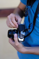 Close up, unrecognizable tourist man is holding an retro camera. Selective focus.
