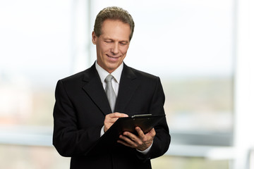 Caucasian businessman writing on clipboard. Mature man in formal wear making a note on black clipboard. People, business, documents.