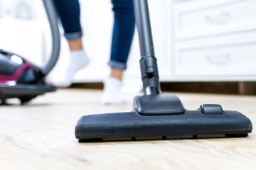 A vacuum cleaner. Room cleaning. Young woman cleaning the floor in the living room with a vacuum cleaner