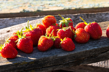 on old boards there are ripe bright strawberry berries in the sun, berries for sale