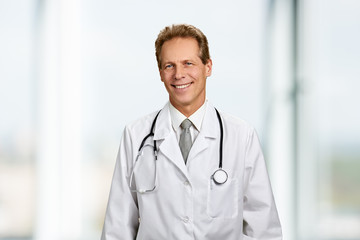 Portrait of happy smiling doctor with stethoscope. Mature male doctor in white coat is smiling on blurred background. People, medicine, profession.