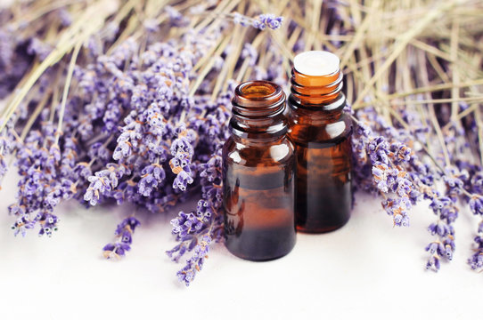 Dropper bottle of lavandula essential oil, bunch of dried purple lavender blossom white table. Herbal aromatherapy & SKincare.