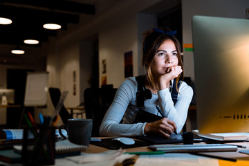Young woman graphic designer using pc computer working with tablet at night in office.