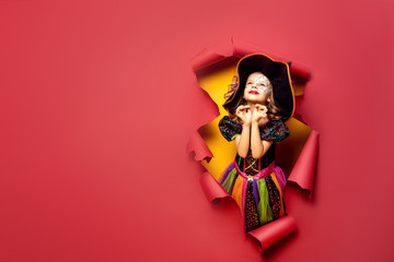 Happy Halloween. Laughing funny child girl in a witch costume of halloween looking through a hole of red and yellow paper background. Copyspace