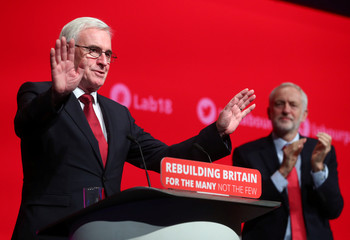 Britain's Labour Party Leader Jeremy Corbyn applauds shadow Chancellor of the Exchequer John McDonnell on stage at the annual Labour Party Conference in Liverpool