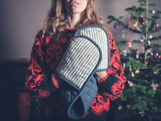 Woman with oven gloves by the christmas tree