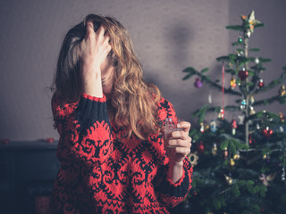 Stressed woman by christmas tree
