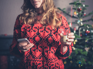 Woman with drink and smartphone at christmas