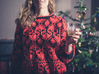 Woman having a drink by the christmas tree