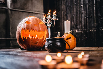 Scary pumpkins and candles on a wooden floor in an old house.