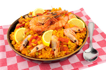 Bowl of fresh seafood paella with shell on prawns isolated on a background