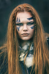 Close up portrait of young redhead northern warrior woman leader with war makeup. Beautiful mighty Viking warrior woman with red hair and green eyes