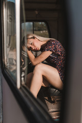 View trough a window of young woman leans her head on a steering wheel of an old van