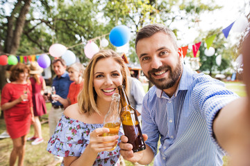 Young couple taking selfie at a party outside in the backyard, clinking bottles.
