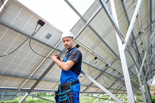 Young engineer technician making electrical wiring standing inside high exterior solar panel photo voltaic system, looking to the camera. Eco friendly cheap electricity generation concept.