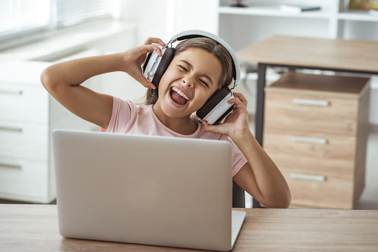 The happy girl in headphones sitting at the desk with a laptop
