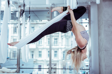 Acrobatic tricks. Attractive nice woman finding correct alignment in pose and hanging upside down