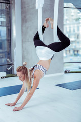 Yoga instructor. Attractive appealing woman placing hands on floor and using hammock