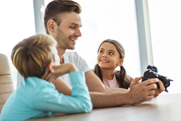 The smiling man with kids holding a camera at the desk