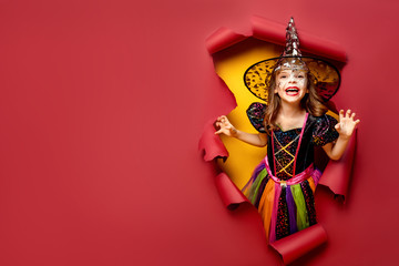 Happy Halloween. Laughing funny child girl in a witch costume of halloween looking, smiling and scares through a hole of red, yellow paper background. Copyspace Fototapete
