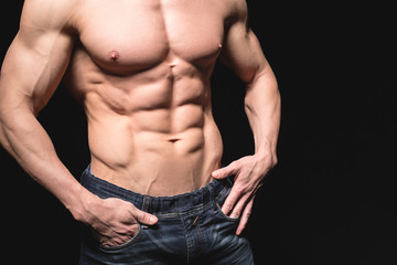 Fitness concept. Muscular and fit torso of young man having perfect abs, bicep and chest. Male hunk with athletic body on black background