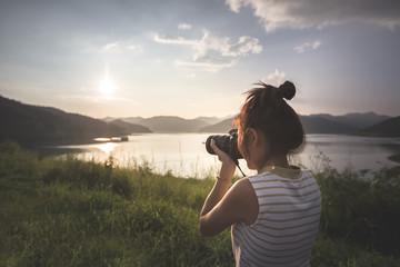 female traveler taking photo of nature view