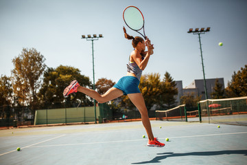 Female tennis player hits the ball with Backhand drive volley.