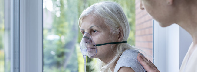 Panorama of weak senior woman with oxygen mask on face in the nursing house