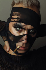 Closeup studio portrait of man smoking cigarette, face of model is partially covered with stockings. Creative makeup fashion art design.