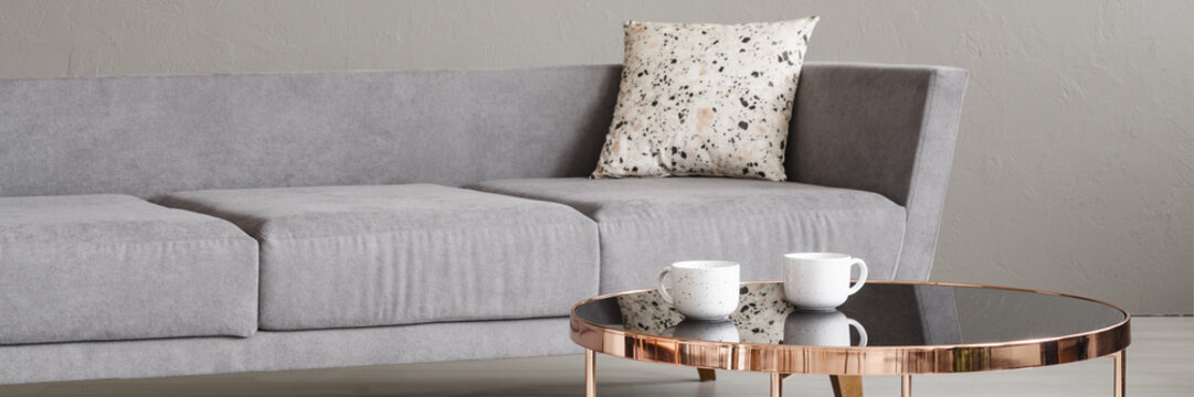 Real photo with close-up of two coffee cups placed on rose gold end table in room interior with grey sofa with lastrico cushion