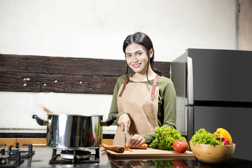 Smiling asian woman cuts the vegetables