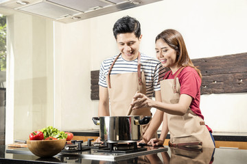 Cheerful asian couple cooking together