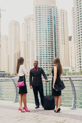 Three business people standing in Dubai Marine and chatting about business plans for next month. One Afro-American man and two European ladies in suits.