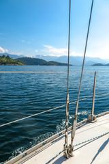 Sailboat sailing over blue sea and blue sky and mountains in background, Angra dos Reis, Rio de Janeiro, Brazil