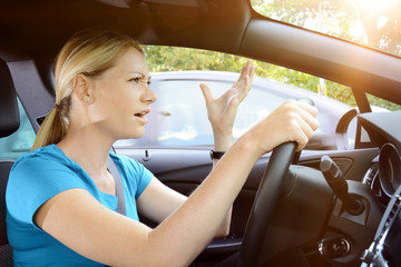 Woman as a car driver is in stress and scolds of annoyance during the car ride