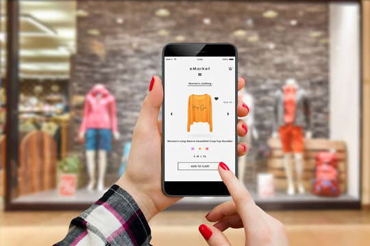 Woman in front of boutique searching for hoodie to buy online on her smartphone