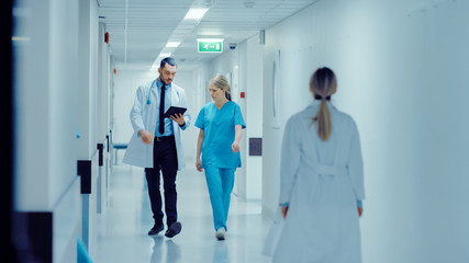 Female Surgeon and Doctor Walk Through Hospital Hallway, They Consult Digital Tablet Computer while Talking about Patient's Health. Modern Bright Hospital with Professional Staff.