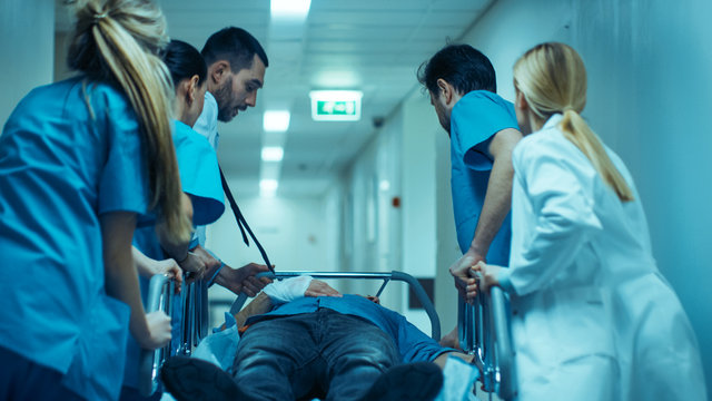 Emergency Department: Doctors, Nurses and Surgeons Move Seriously Injured Patient Lying on a Stretcher Through Hospital Corridors. Medical Staff in a Hurry Move Patient into Operating Theater.