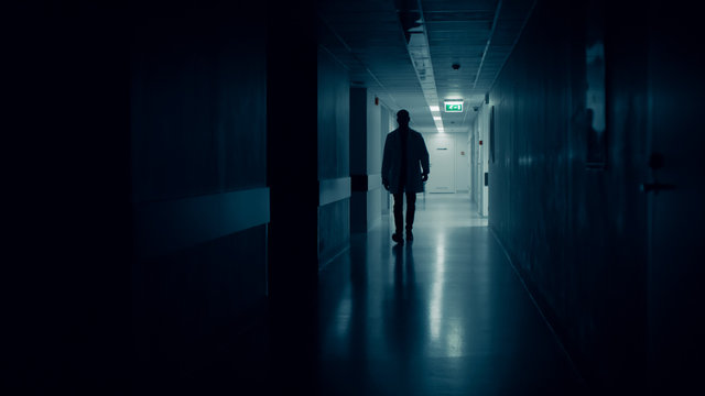 Medical Doctor Silhouette Walks in Dark Part of the Hospital Corridor.