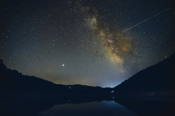 Starry sky with Milky Way over the mountain lake