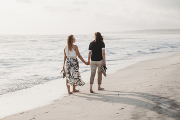 Young couple in love walking on the deserted beach on a summer evening. Two women hold hands by the sea
