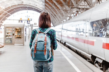 A young tourist girl with backpack waits for train on railway station