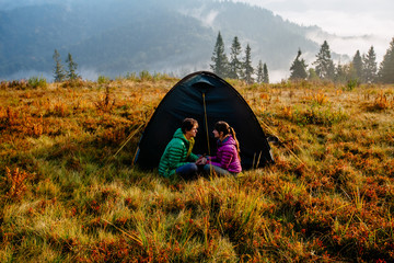 Side view of a happy lovely couple traveler sitting at entrance to tent. Man and woman enjoying morning fall season in mountains autumn landscape.